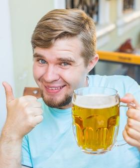 Uomo sorridente allegro che tiene un grande boccale di birra e mostra i pollici in su all'aperto