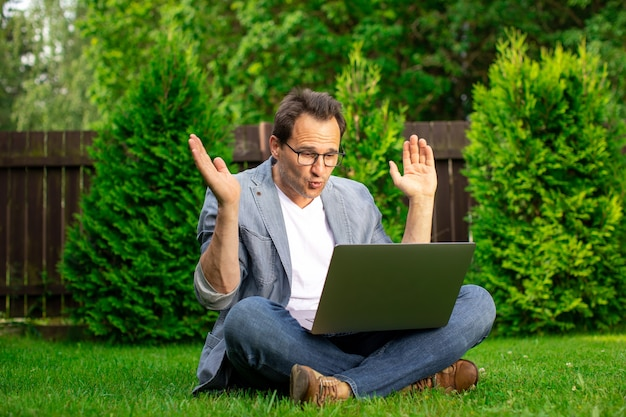 Uomo d'affari di mezza età sorpreso gioioso si siede sull'erba lavora all'aperto, guarda con sorpresa allo schermo del laptop, uomo felice con la crescita delle scorte e profitti più elevati, vincitore, concetto di successo, spazio di copia