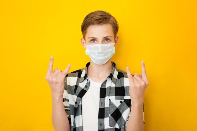 Ragazzo teenager allegro in vestiti alla moda che mostrano con le corna delle braccia alzate o il gesto della roccia