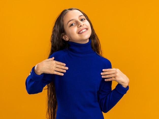 Adolescente gioiosa che guarda davanti indicando se stessa isolata sulla parete arancione