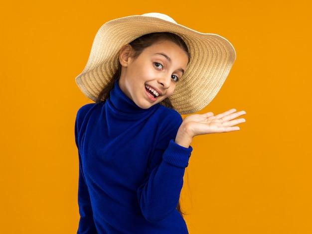 Adolescente gioiosa che indossa il cappello da spiaggia che mostra la mano vuota guardando la parte anteriore isolata sulla parete arancione