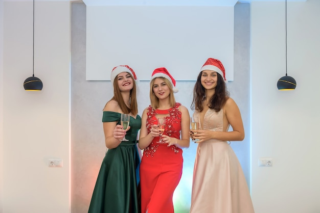 Tre donne allegre con bicchieri di champagne in posa sulla festa. capodanno e festa di natale
