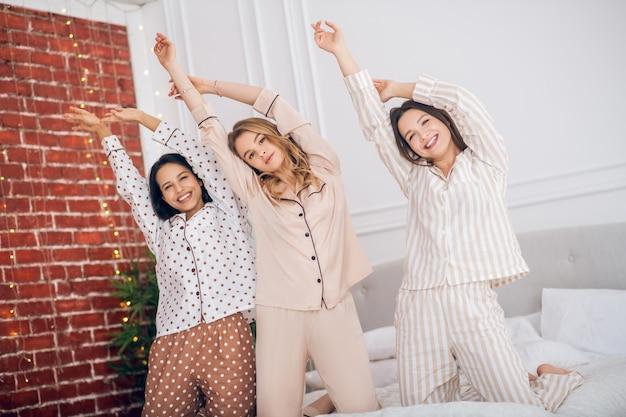 Gioioso. tre ragazze che hanno un pigiama party e si sentono gioiose