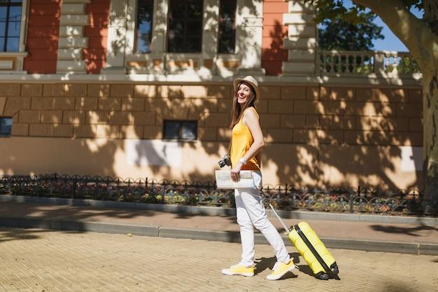 Donna turistica gioiosa del viaggiatore in cappello giallo dell'abbigliamento casual di estate con la mappa della città della valigia che cammina in città all'aperto. ragazza che viaggia all'estero per viaggiare nel fine settimana. concetto di stile di vita del viaggio turistico.