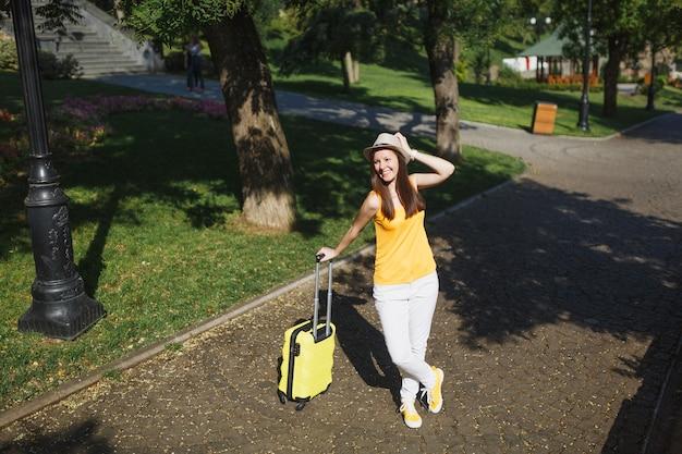 Gioiosa donna turistica viaggiatrice in abiti casual estivi gialli con valigia che tiene la mano vicino al cappello, cammina in città all'aperto. ragazza che viaggia all'estero per viaggiare nei fine settimana. stile di vita del viaggio turistico.