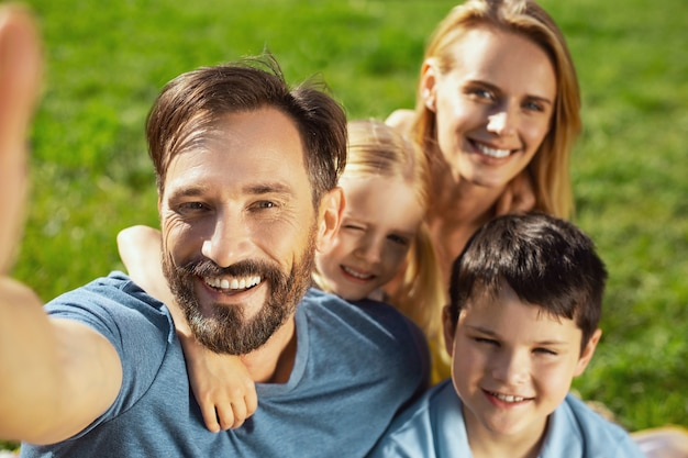 Uomo allegro e ben costruito che sorride e che prende i selfie con la sua famiglia