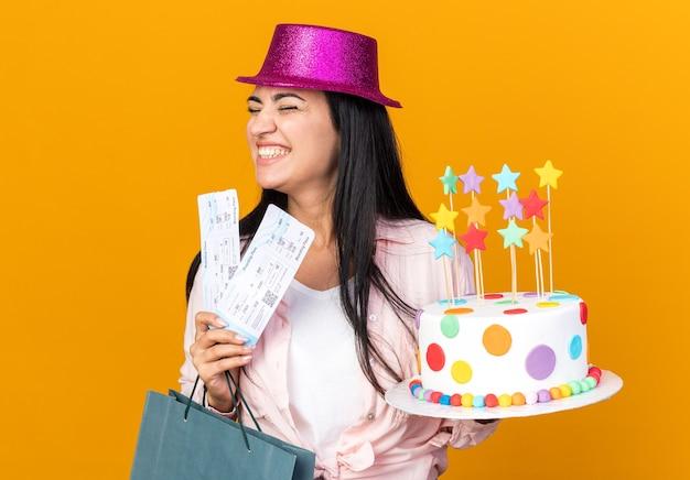 Gioiosa con gli occhi chiusi giovane bella ragazza che indossa un cappello da festa con una borsa regalo con torta e biglietti