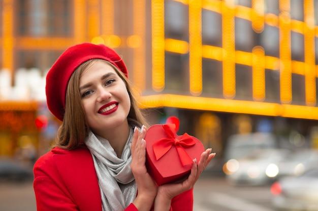 Donna allegra che tiene in mano una confezione regalo di san valentino a forma di cuore con un fiocco su uno sfondo di luci sfocate. spazio vuoto