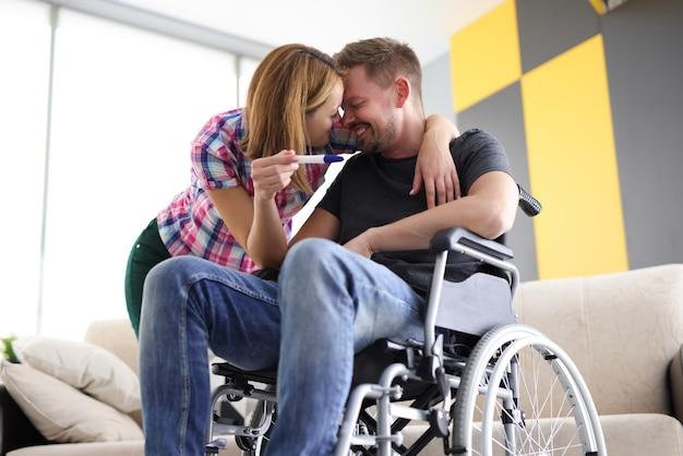 Donna allegra e uomo in sedia a rotelle con test di gravidanza