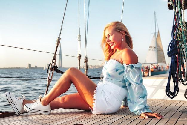 Ritratto di donna gioiosa di mezza età sul ponte dello yacht a vela che si gode il viaggio in acqua durante la crociera costiera estiva. donna di affari femminile sulla barca a vela durante il tramonto. concetto di viaggio avventura, yachting e vacanza