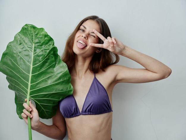 La donna allegra che mostra la lingua in tropici della foglia verde del costume da bagno ha isolato il fondo