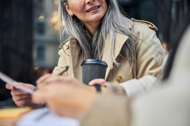 Donna allegra che studia documenti con un collega in un caffè all'aperto