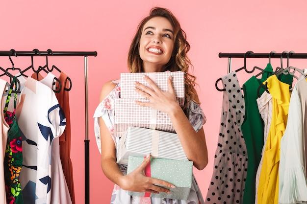 Gioiosa donna che indossa un abito in piedi in negozio vicino a stendibiancheria con scatole presenti isolato su rosa