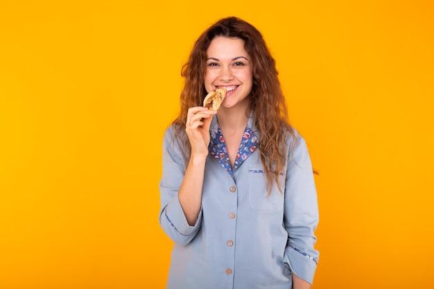 La donna allegra indossa il pigiama di moda andando a mangiare un piccolo delizioso croissant su sfondo giallo con