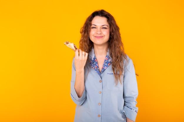 La donna allegra indossa il pigiama di moda andando a mangiare piccoli deliziosi croissant