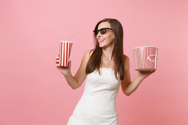 Donna gioiosa in abito bianco, occhiali 3d che guardano film, con secchio di popcorn, bicchiere di plastica di soda o cola