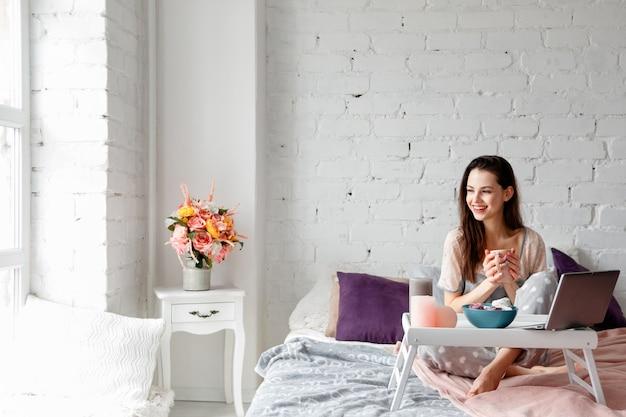 Donna allegra con una tazza di caffè a letto.
