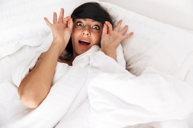 Donna allegra con i capelli scuri sorridente, mentre dorme nel letto con maschera su lino bianco
