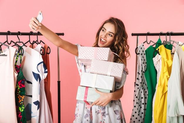Donna allegra con acquisto in piedi in negozio vicino a stendibiancheria e tenendo selfie sul cellulare isolato in rosa