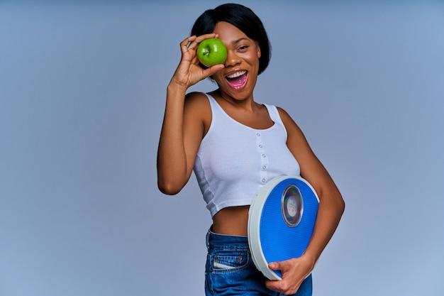 Donna allegra con scaglie viola che si nasconde dietro una mela verde in mano. concetto di dieta