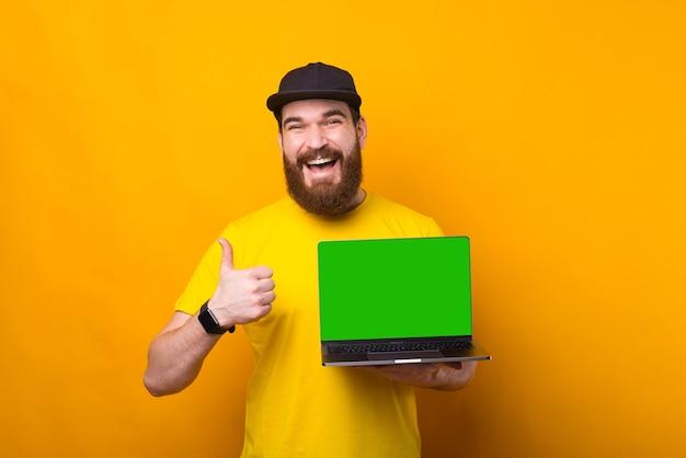 Gioioso giovane barbuto hipster uomo che mostra pollice in alto e schermo verde sul computer portatile