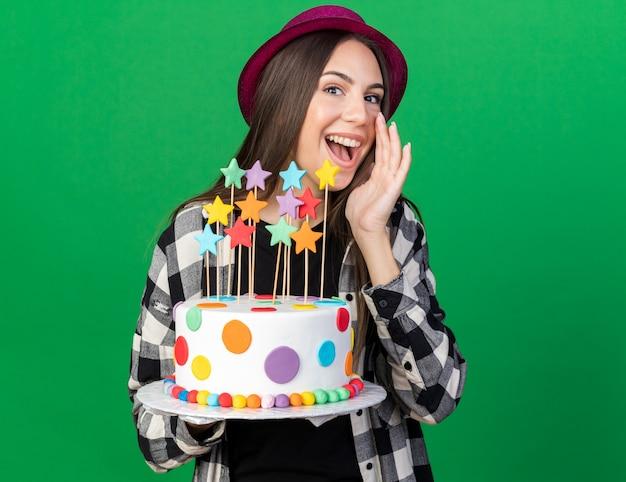 Gioiosa giovane bella ragazza che indossa un cappello da festa con in mano una torta che chiama qualcuno