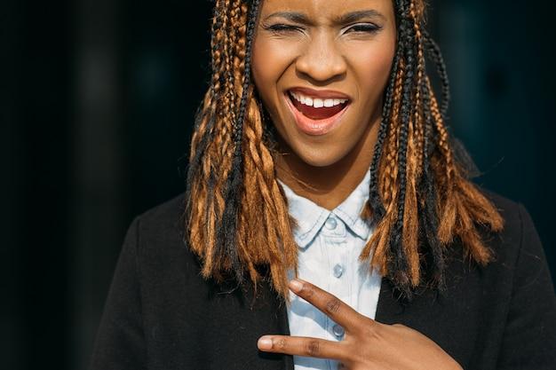 Gioiosa giovane donna nera. gesto di vittoria. felice donna afroamericana, modello elegante in posa su sfondo scuro, concetto di felicità