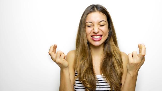 Gioiosa giovane donna bruna stringe i denti, alza le dita incrociate