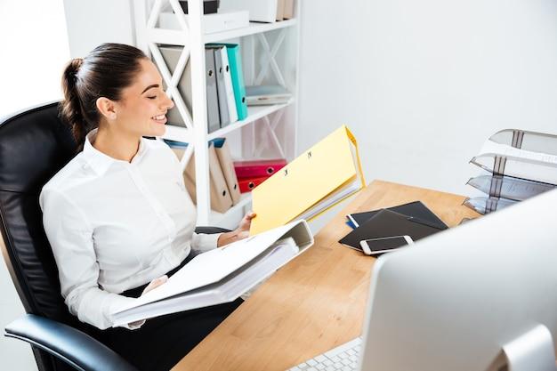 Gioiosa giovane donna d'affari che guarda le cartelle gialle mentre è seduta alla scrivania dell'ufficio