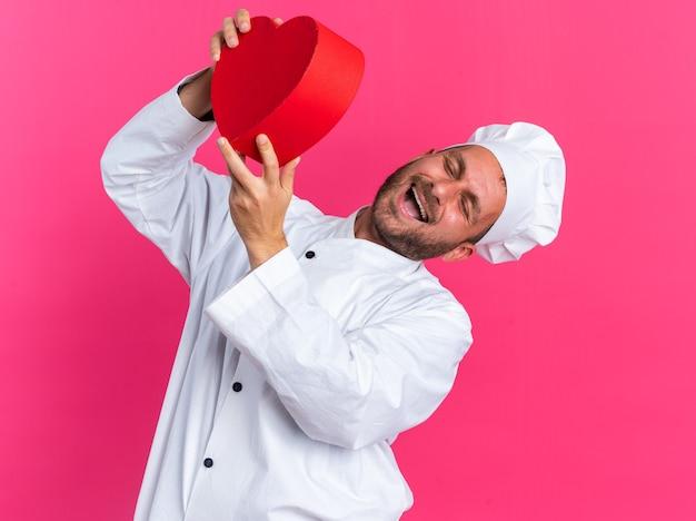Gioioso giovane maschio caucasico cuoco in uniforme da chef e berretto che tiene a forma di cuore inclinando la testa a lato ridendo con gli occhi chiusi isolati su parete rosa