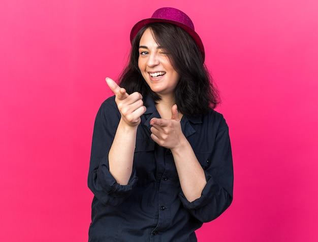 Gioiosa giovane donna caucasica da festa che indossa un cappello da festa che guarda l'occhiolino anteriore facendo un gesto isolato sulla parete rosa pink