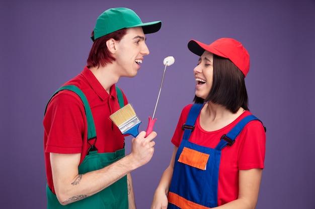 Gioiosa giovane coppia in uniforme da operaio edile e berretto che tiene rullo di vernice e pennello guardando una ragazza e una ragazza che ridono con gli occhi chiusi