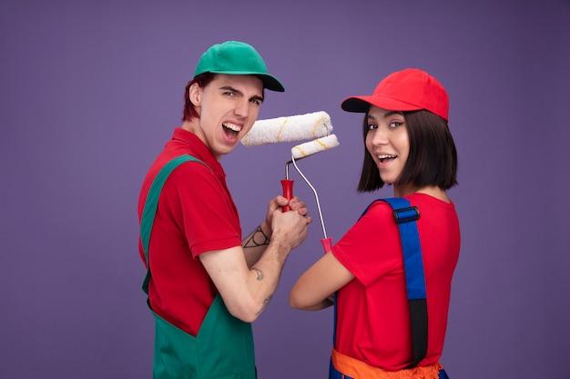 Gioiosa giovane coppia in uniforme da operaio edile e berretto in piedi nella vista di profilo ragazza in piedi dietro la vista che tiene il rullo di vernice che guarda l'obbiettivo isolato sul muro viola