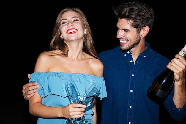 Gioiosa giovane coppia che tiene bicchieri e bottiglia di champagne e ride di notte