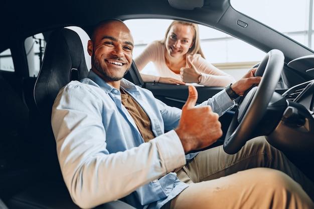 Gioiosa coppia giovane guardandosi intorno all'interno di una nuova auto che stanno per acquistare in una concessionaria di un negozio di auto