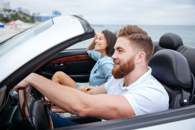 Giovani coppie allegre che sorridono mentre guidano nella loro automobile convertibile