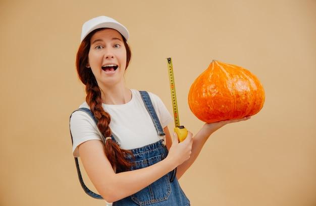 La gioiosa giovane contadina misura le grandi dimensioni di un raccolto di zucca con un metro a nastro