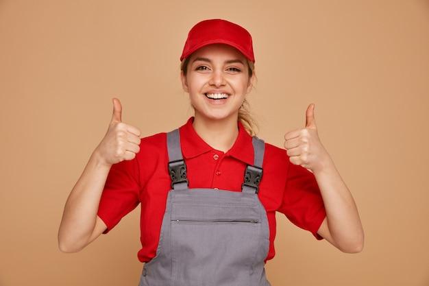 Gioioso giovane operaio edile femminile che indossa l'uniforme e cappuccio che mostra i pollici in su