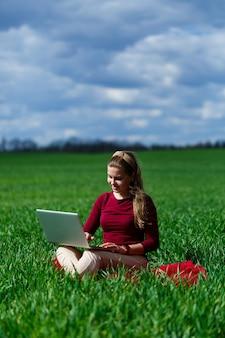 Ragazza allegra sull'erba con un computer portatile in grembo. alzò le mani e rise. felicità nello stile di vita di uno studente classico. lavora sulla natura. riposa dopo una buona giornata di lavoro.