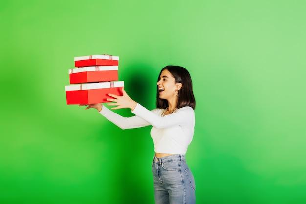 Gioiosa ragazza giovane vomitare scatole rosse con doni presenti su sfondo verde