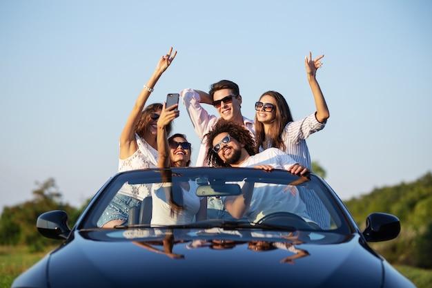 Giovani ragazze e ragazzi allegri in occhiali da sole sono seduti in una cabriolet nera sulla strada alzando le mani e facendo selfie in una giornata di sole. .