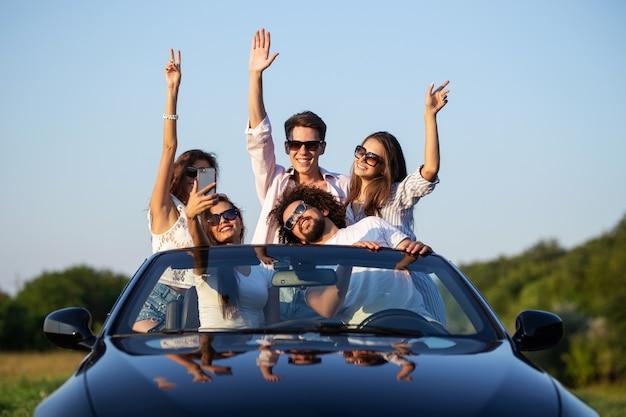 Gioiose ragazze e ragazzi in occhiali da sole sono seduti in una cabriolet nera sulla strada alzando le mani e sorridendo in una giornata di sole. .