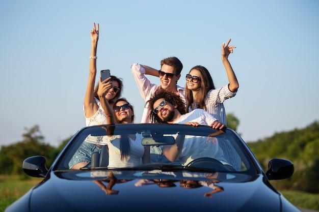 Giovani ragazze e ragazzi gioiosi in occhiali da sole sono seduti in un'auto decappottabile nera sulla strada alzando le mani e facendo selfie in una giornata di sole. .