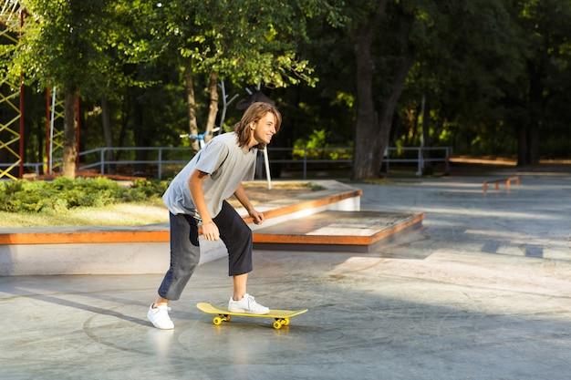 Gioioso giovane ragazzo che trascorre del tempo allo skate park, cavalcando uno skateboard