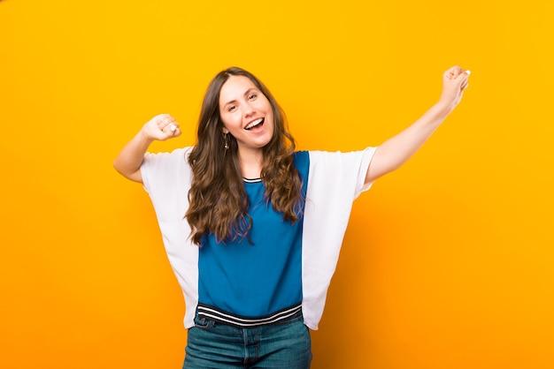 La giovane donna allegra sta facendo il gesto del vincitore mentre sorride alla telecamera.