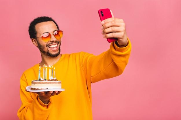 Gioioso giovane uomo che soffia candele su una torta di compleanno isolata sul colore rosa. utilizzando il telefono cellulare.