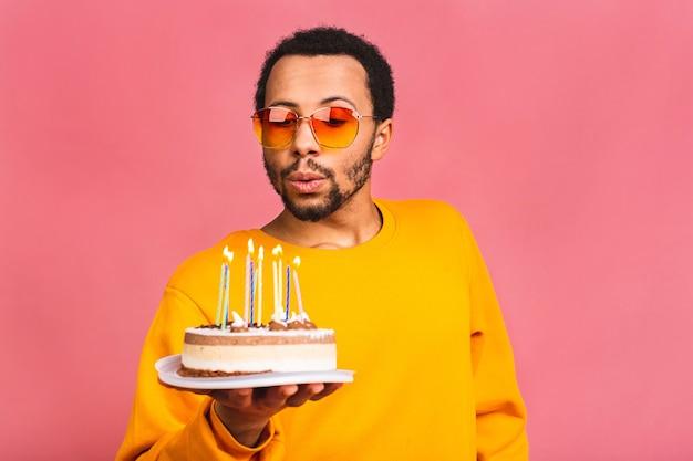 Gioioso giovane uomo che soffia candele su una torta di compleanno isolata sul colore rosa.