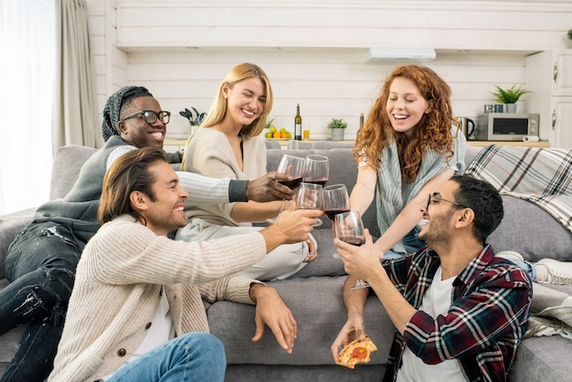 Gioiosi giovani amici multiculturali tintinnano con bicchieri di vino rosso mentre fanno brindisi dal divano a casa festa