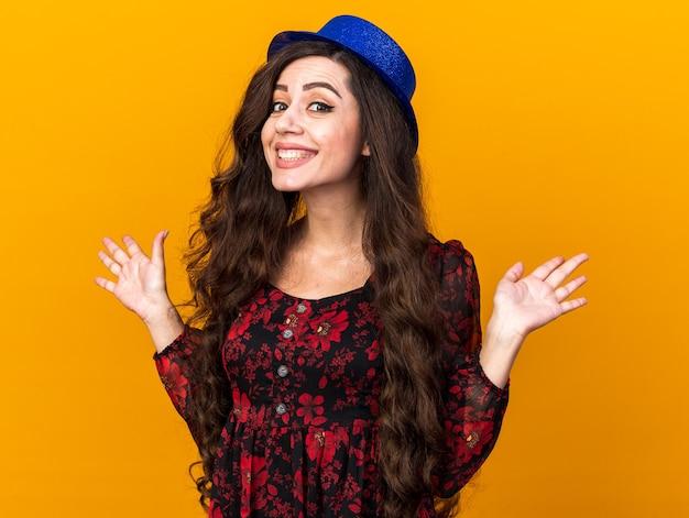 Giovane ragazza allegra che indossa un cappello da festa che mostra le mani vuote isolate sulla parete arancione Foto Premium