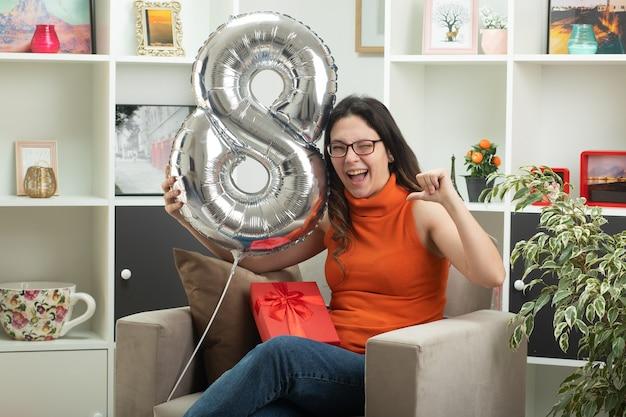 Gioiosa giovane bella donna con gli occhiali che tiene e indica a forma di palloncino otto seduto sulla poltrona in soggiorno a marzo giornata internazionale della donna